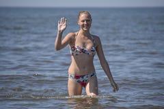 Blond flicka i en bikini som kommer ut ur havsvattnet Härlig ung kvinna i en färgrik bikini på havsbakgrund Royaltyfri Bild