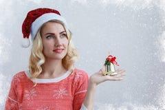 Blond flicka i en julhatt med en klocka i händer på en ljus bakgrund royaltyfri foto