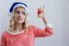 Blond flicka i en julhatt med en klocka i händer på en ljus bakgrund royaltyfri fotografi