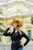 Blond flicka i en krans av lönnlöv Royaltyfria Bilder