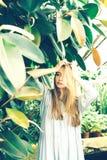Blond flicka i en tropisk buske i växthuset arkivbild