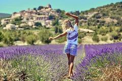 Blond flicka i ett brett fält av lavendel arkivfoton