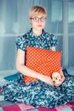 Blond flicka i ett glass sammanträde på en röd kudde för fönster och för innehav och innehavskallen Royaltyfria Bilder
