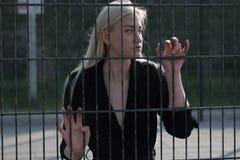blond flicka i ett svart lag bak ett metallstaket Arkivbilder