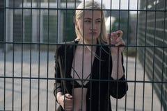 blond flicka i ett svart lag bak ett metallstaket Arkivfoton