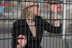 blond flicka i ett svart lag bak ett metallstaket Royaltyfri Bild