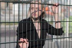 blond flicka i ett svart lag bak ett metallstaket Arkivbild