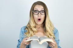 Blond flicka i förvånade exponeringsglas rymma boken royaltyfria bilder