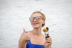 Blond flicka i hipsterexponeringsglas som tummar med makeup royaltyfria foton