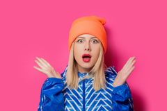 Blond flicka i sportomslag och hatt arkivfoton