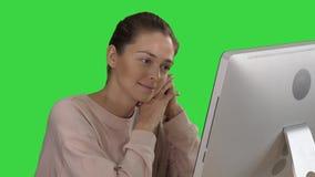 Blond flicka med den rosa sweatern som ser bildskärmen av den hållande ögonen på videoen för dator på en grön skärm, chromatangen stock video