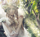Blond flicka med den utsmyckade blommahatten royaltyfria bilder