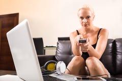 Blond flicka med en fjärrkontroll Arkivbilder