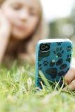 Blond flicka med en mobil telefon Fotografering för Bildbyråer