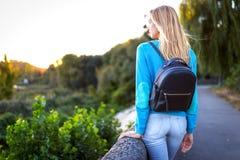 Blond flicka med en stående ryggsäck tillbaka Royaltyfri Fotografi