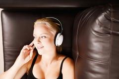 Blond flicka med hörlurar Arkivbild