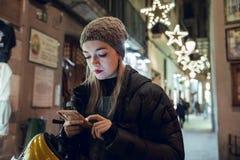 Blond flicka med hatten genom att använda mobiltelefonen arkivbild