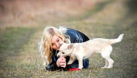 Blond flicka med hennes valp Royaltyfri Fotografi