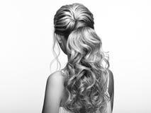 Blond flicka med långt och skinande lockigt hår arkivfoto