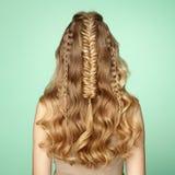 Blond flicka med långt och skinande lockigt hår royaltyfri foto