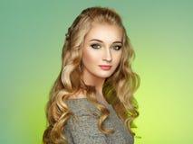 Blond flicka med långt och skinande lockigt hår royaltyfri fotografi