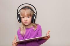 Blond flicka med minnestavlan och hörlurar med mikrofon royaltyfria foton