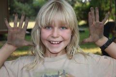 Blond flicka med smutsiga händer Arkivbild