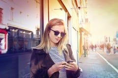 Blond flicka med telefonen royaltyfria bilder