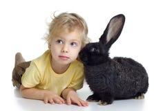 Blond flicka och svart kanin Arkivbilder
