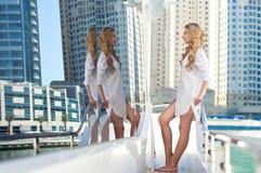 Blond flicka på en yacht, skyskrapor som en bakgrund royaltyfri fotografi