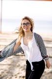 Blond flicka på stranden av den sandiga stranden vid havet Royaltyfria Foton