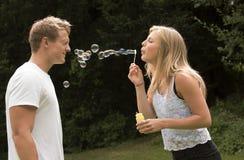 Blond flicka som blåser bubblor Fotografering för Bildbyråer