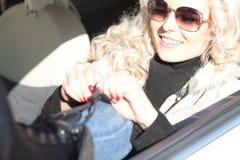 Blond flicka som gör upp i hennes bil Arkivbild