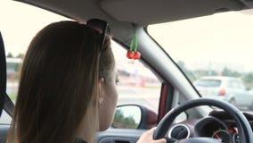 Blond flicka som kör en bil, en ursnygg solsignalljus och gradera Tillfälliga exponeringsvariationer orsakas av vägmärkena stock video