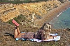 Blond flicka som läser en bok Arkivfoto