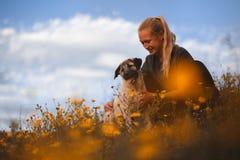 Blond flicka som spelar med den spanska mastiffen f?r valp i ett f?lt av gula blommor arkivbild