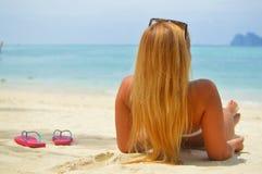 Blond flicka som suntanning på stranden Fotografering för Bildbyråer