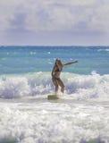 Blond flicka som surfar vågorna Arkivbild