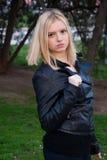 Blond flicka som utomhus poserar i läderomslag Fotografering för Bildbyråer