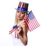Blond flicka som vinkar den isolerade lilla amerikanska flaggan Arkivbild