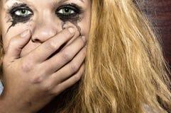 Blond flickacovering henne mun Arkivbilder