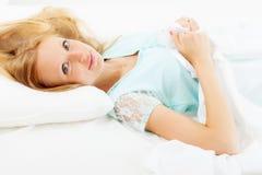Blond   Frau, die auf weißem Blatt liegt Lizenzfreie Stockbilder