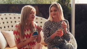 Blond friends sip drinks colored red and blue. While seated on trendy furnishings in outdoor cafe stock video