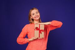 Blond with gift box. Isolated on violet background Stock Image