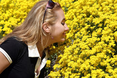 Blond girl. Smelling yellow flowers Stock Photos