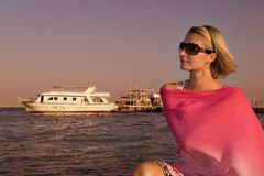 Blond girl. Picture of a young gorgeous girl sitting near yachts Stock Photos