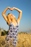 Blond girl. Beautiful blond girl stretching in the wheat field Royalty Free Stock Photo