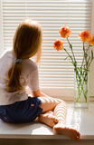Blond girl. Young blond girl sitting on a window-sill Royalty Free Stock Photo
