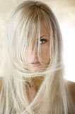 The blond girl. Fashion portrait of a cute blond girl with long hair on yellow background Royalty Free Stock Photo