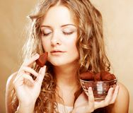 Blond girl in act to eat a chocolate candy Stock Images